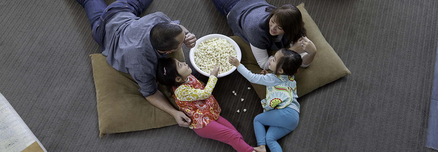 Family eating popcorn on Stainmaster carpet.